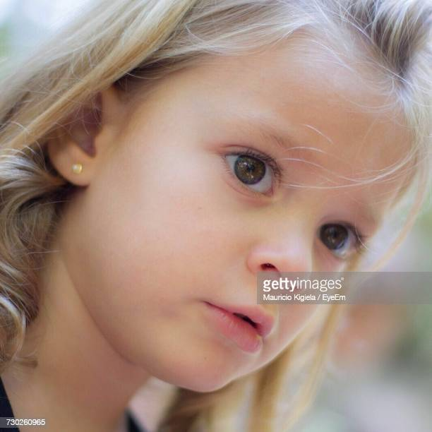 Close-Up Of Cute Girl With Blond Hair Looking Away