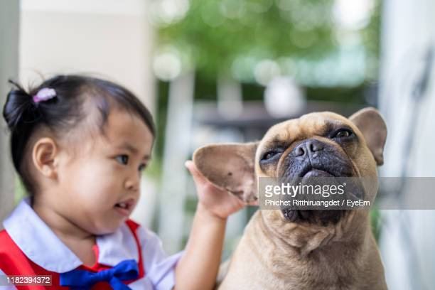 close-up of cute girl with dog outdoor - phichet ritthiruangdet stock photos and pictures