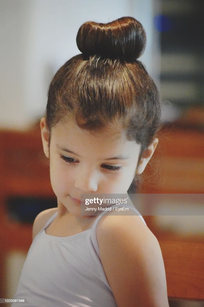 closeup of cute girl with hair bun looking down at home ストック