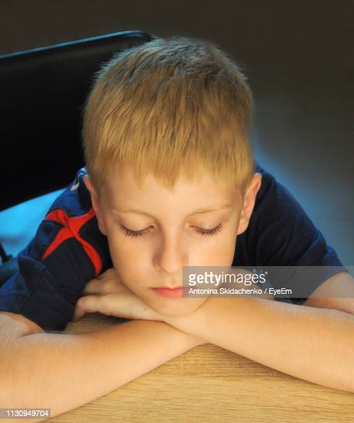 Close-Up Of Cute Sad Boy Resting Head On Table At Home