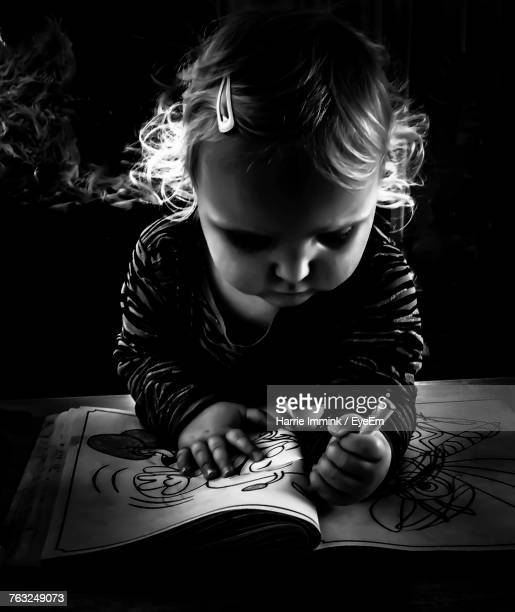Close-Up Of Cute Toddler Girl Drawing On Book In Darkroom