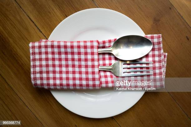 close-up of cutlery and napkin in plate on table - serviette stock-fotos und bilder