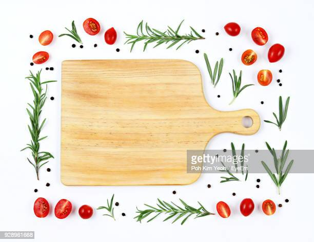 close-up of cutting board amidst ingredients over white background - cooking utensil stock photos and pictures