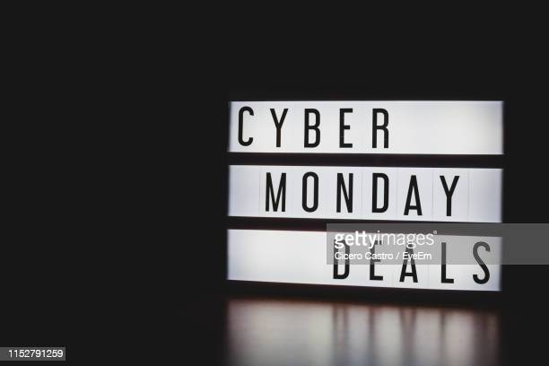 close-up of cyber monday deals text on information sign against black background - cyber monday stock pictures, royalty-free photos & images