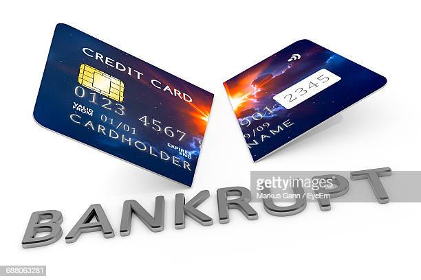 Close-Up Of Damaged Credit Card By Text On White Background