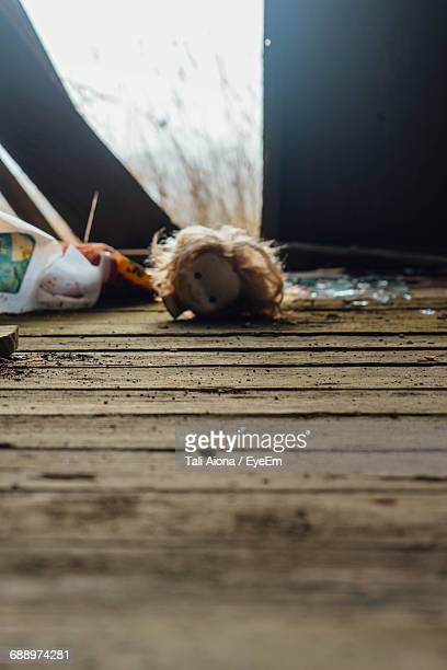 Close-Up Of Damaged Doll Fallen On Floor