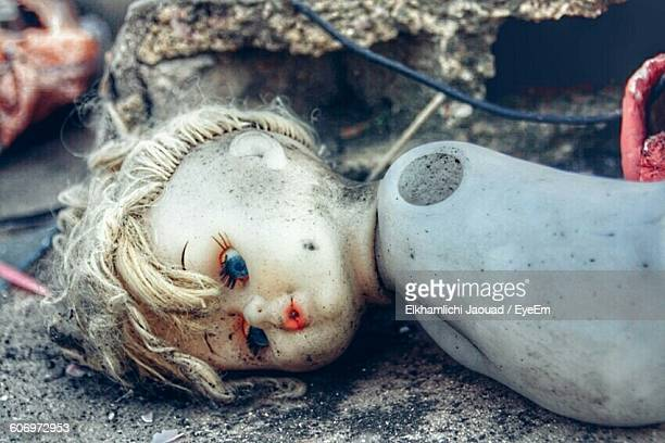 Close-Up Of Damaged Doll On Sand