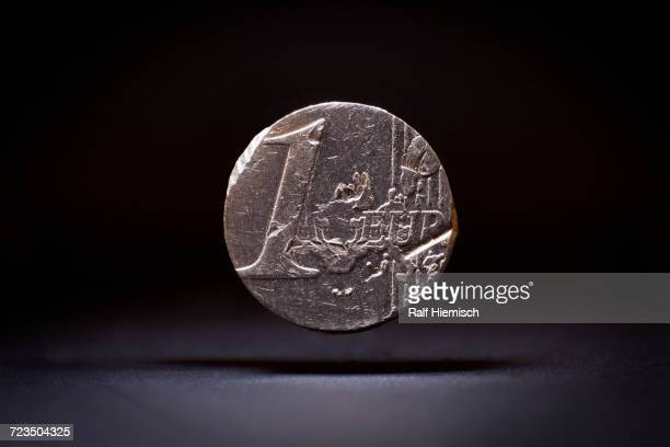 Close-up of damaged one euro coin levitating against black background