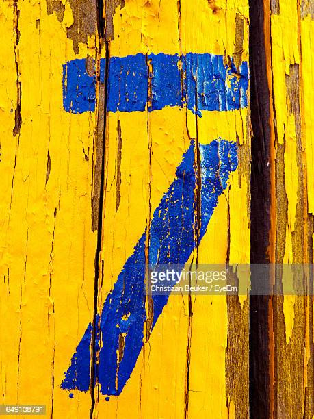 Close-Up Of Damaged Paint With Number 7 On Yellow Wood