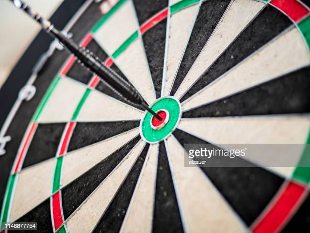 close-up of dart hitting the bullseye - target center stock pictures, royalty-free photos & images