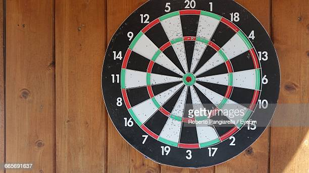 close-up of dartboard mounted on wooden wall - dartboard stock pictures, royalty-free photos & images