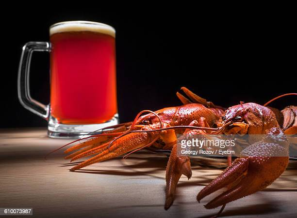 Close-Up Of Dead Lobsters And Beer Mug On Table Against Black Background