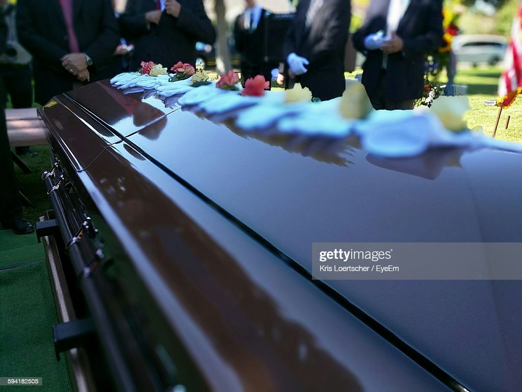 Close-Up Of Decorated Coffin Against Men At Funeral : Stock Photo