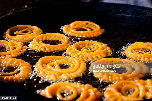 Close-up of delicious jalebis frying in oil pan at stall