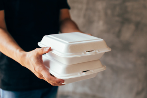 Close-up of delivery man handing a slack of foam lunch box 1137764161