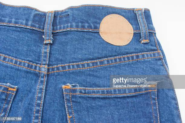 close-up of denim against white background - trousers stock pictures, royalty-free photos & images