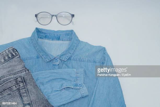 close-up of denim shirt and jeans by eyeglasses against white background - デニムシャツ ストックフォトと画像