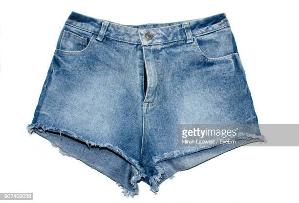 close-up of denim shorts over white background - denim shorts stock pictures, royalty-free photos & images