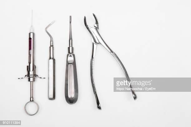 Close-Up Of Dental Instruments Over White Background