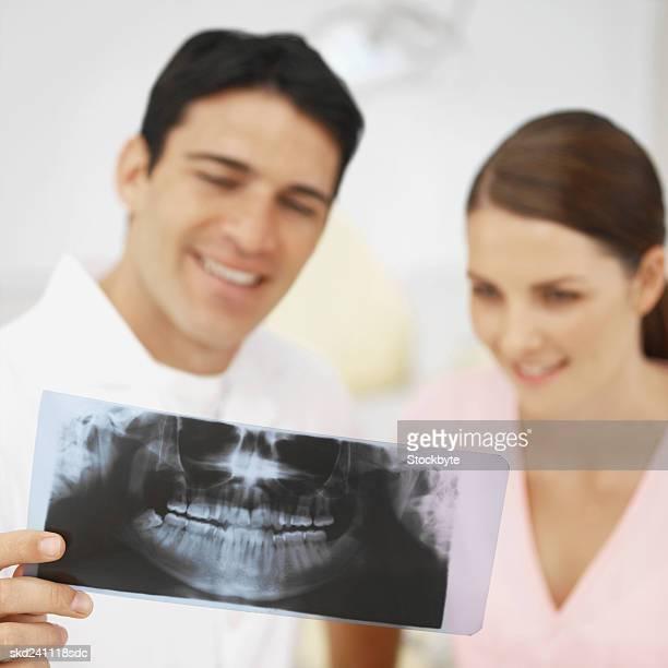Close-up of dentist and dental nurse examining x-ray