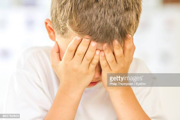 Close-Up Of Depressed Boy Covering Face With Hands