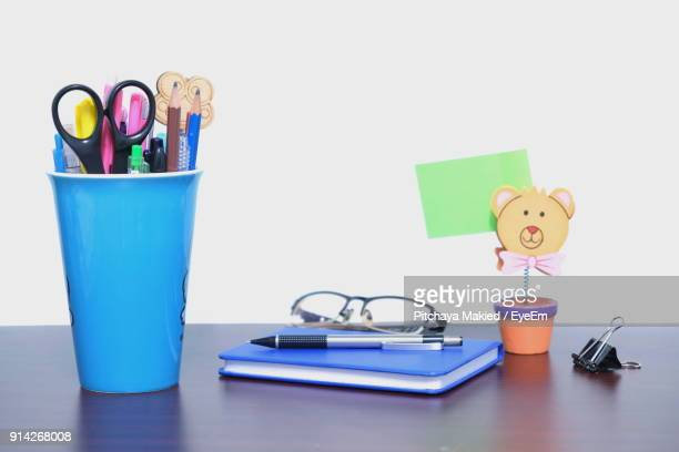 Close-Up Of Desk Organizer By Diary On Table Against White Background