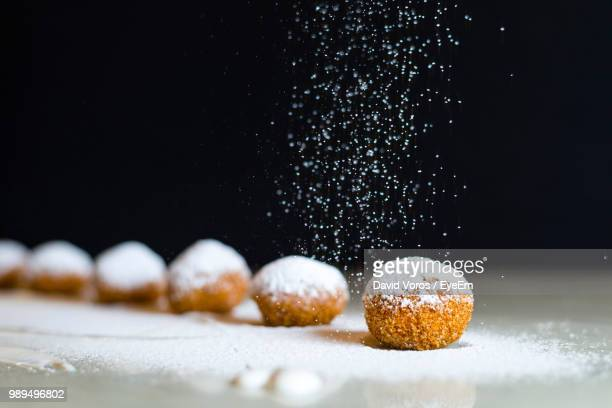 close-up of dessert on table against black background - icing sugar stock pictures, royalty-free photos & images