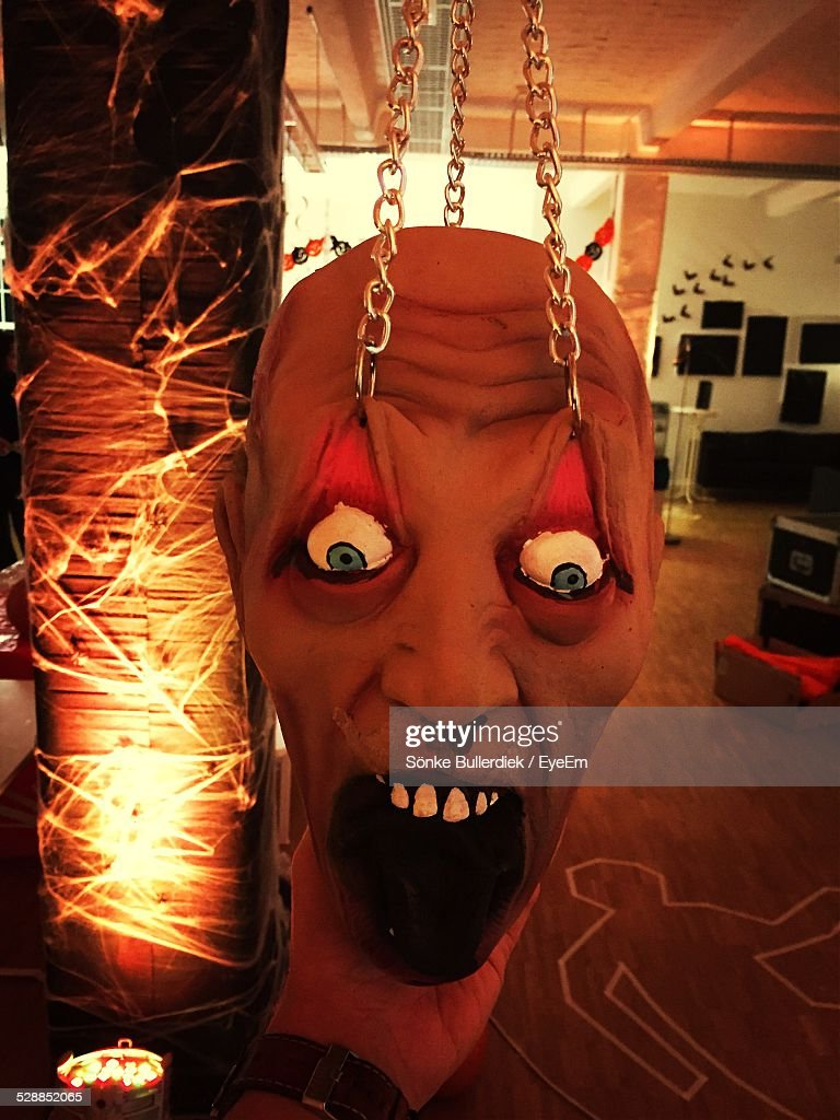 Close-Up Of Devil Mask Hanged By Chain At Home : Stock Photo