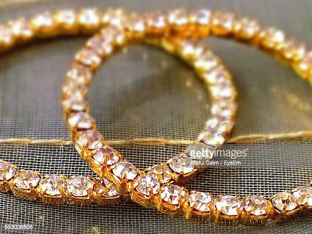 Close-Up Of Diamond Bangles On Bed