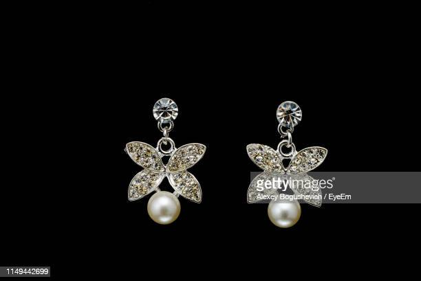 close-up of diamond earrings against black background - ohrring stock-fotos und bilder