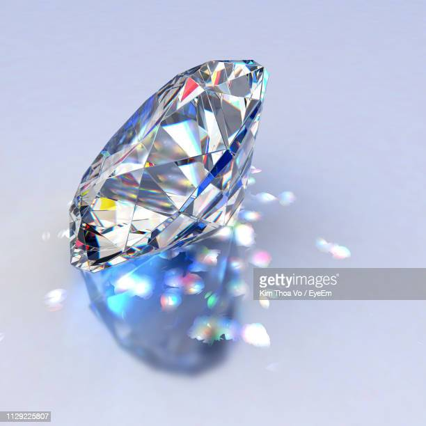 close-up of diamond on gray background - diamond gemstone stock pictures, royalty-free photos & images