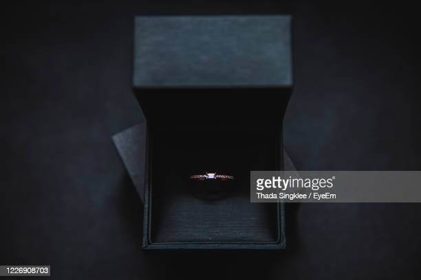 close-up of diamond ring in box on black background - expense stock pictures, royalty-free photos & images