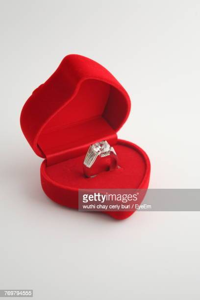 Close-Up Of Diamond Ring In Red Jewelry Box Over White Background
