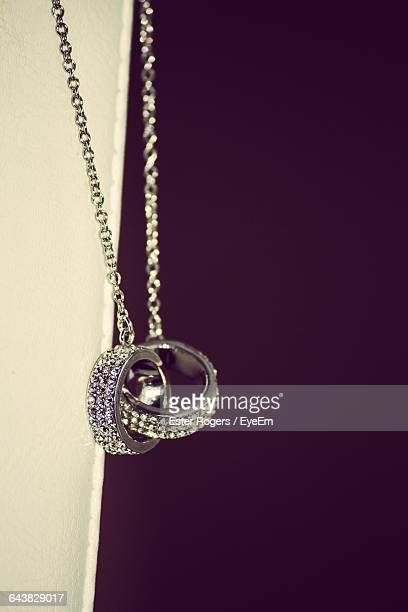 Close-Up Of Diamond Ring Necklace Against Black Background
