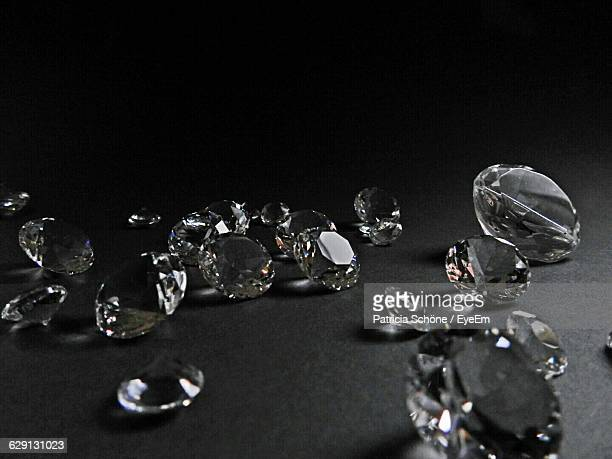 Close-Up Of Diamonds On Table Against Black Background