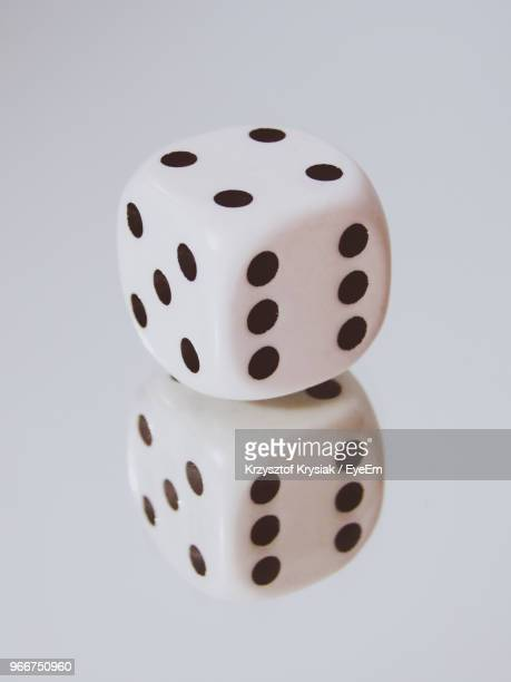 Close-Up Of Dice Reflecting Over White Background