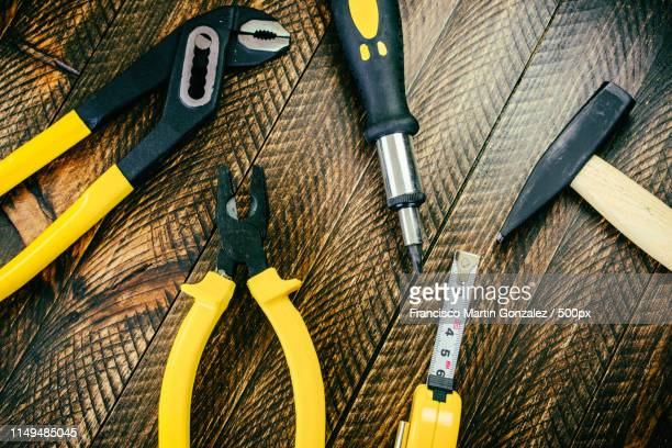 Close-Up Of Different Working Tools On Wooden Table