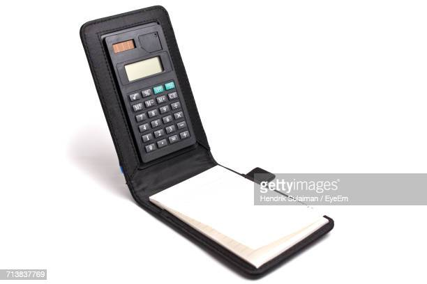 Close-Up Of Digital Calculator With Diary On White Background