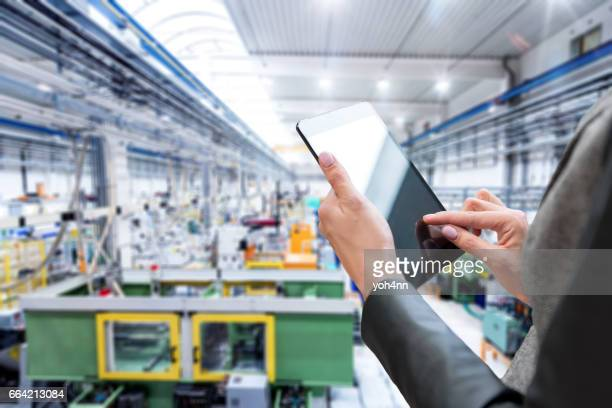 Close-up of digital tablet & futuristic factory