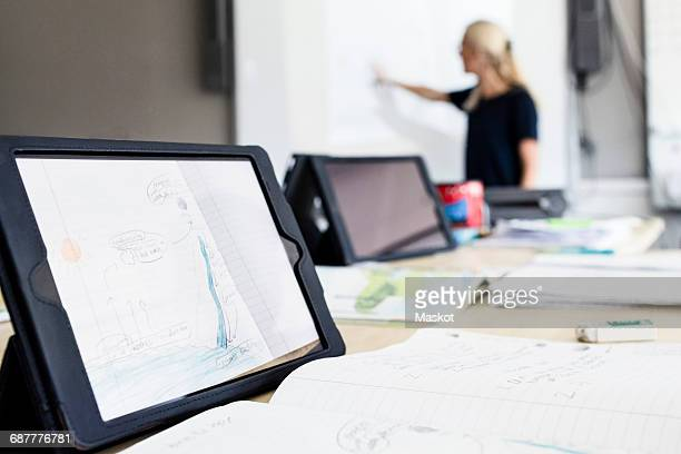 Close-up of digital tablet on desk with teacher explaining in background