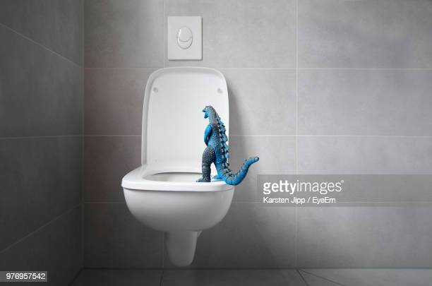 close-up of dinosaur toy on toilet bowl in bathroom - toilet bowl stock photos and pictures