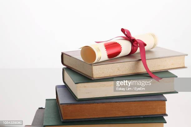 close-up of diploma on stacked books against white background - graduation background stock pictures, royalty-free photos & images
