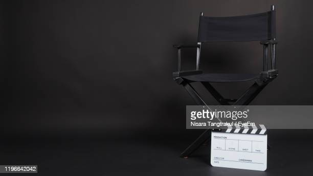 close-up of directors chair with movie clapper against black background - director's chair stock pictures, royalty-free photos & images