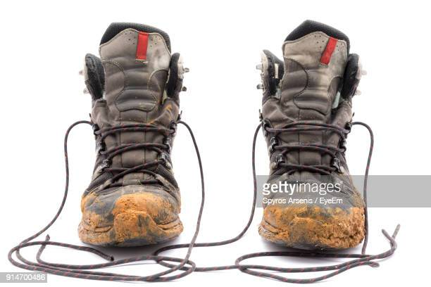 Close-Up Of Dirty Shoes Against White Background