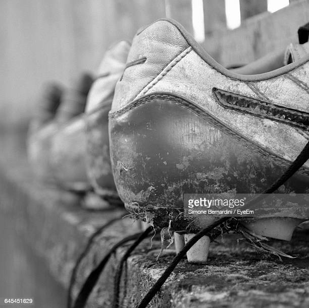 Close-Up Of Dirty Soccer Shoes On Retaining Wall