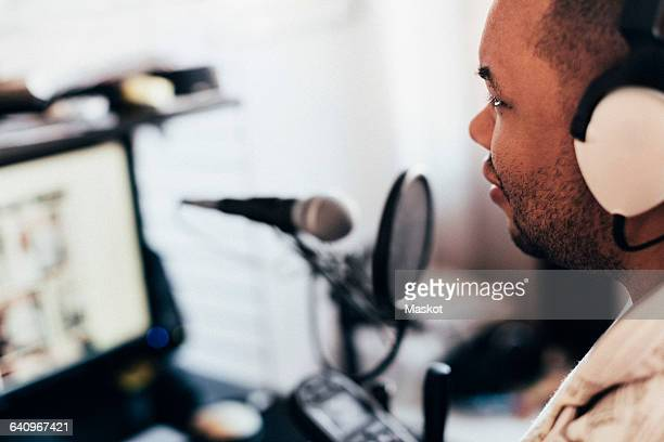 Close-up of disabled musician with headphones in recording studio