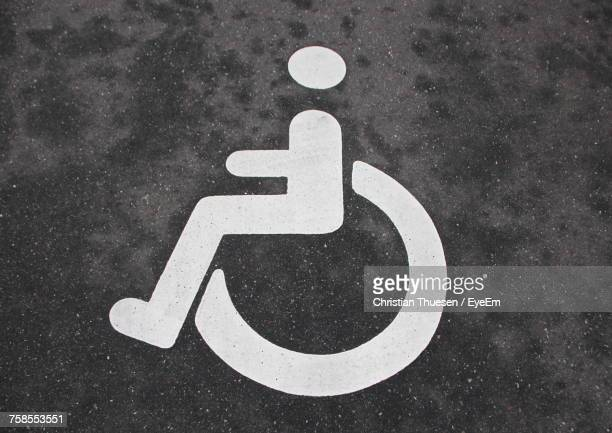 close-up of disabled sign on road - disabled sign stock photos and pictures