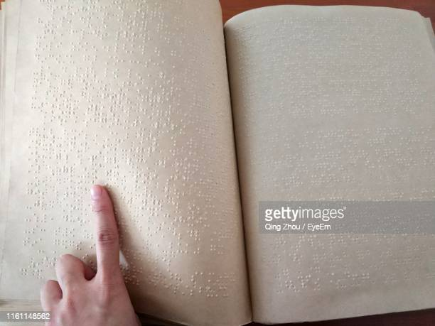 close-up of disables person hand reading book on table - menschlicher finger stock-fotos und bilder