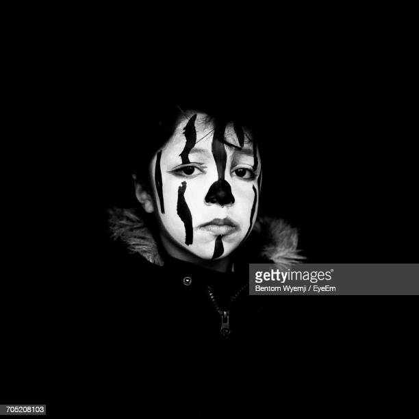 Close-Up Of Disguised Boy With Face Paint Against Black Background