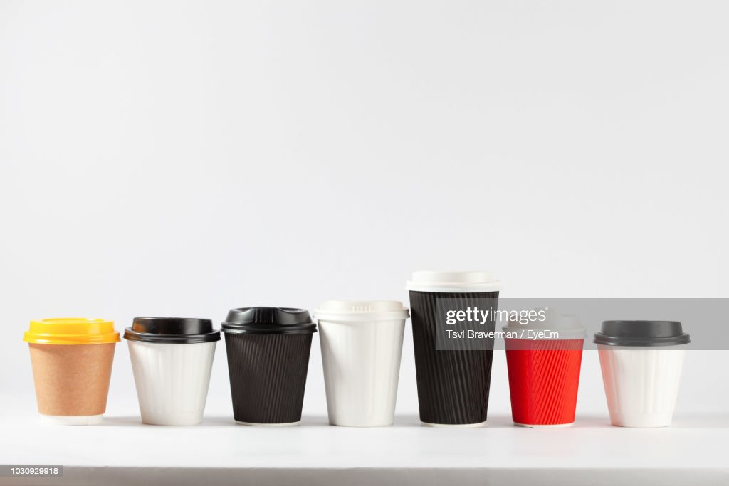 Close-Up Of Disposable Coffee Cups Over White Background : Stock Photo